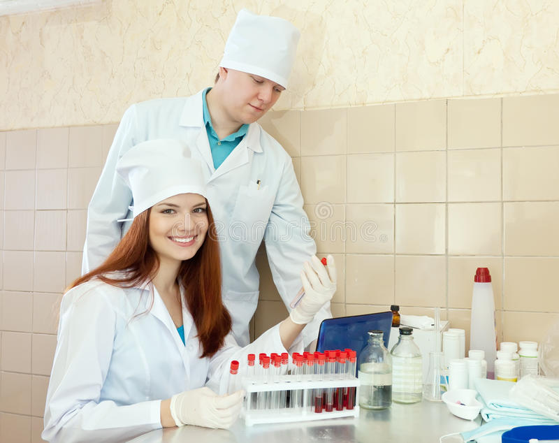 Twee werkers uit de gezondheidszorg in medisch laboratorium stock afbeeldingen