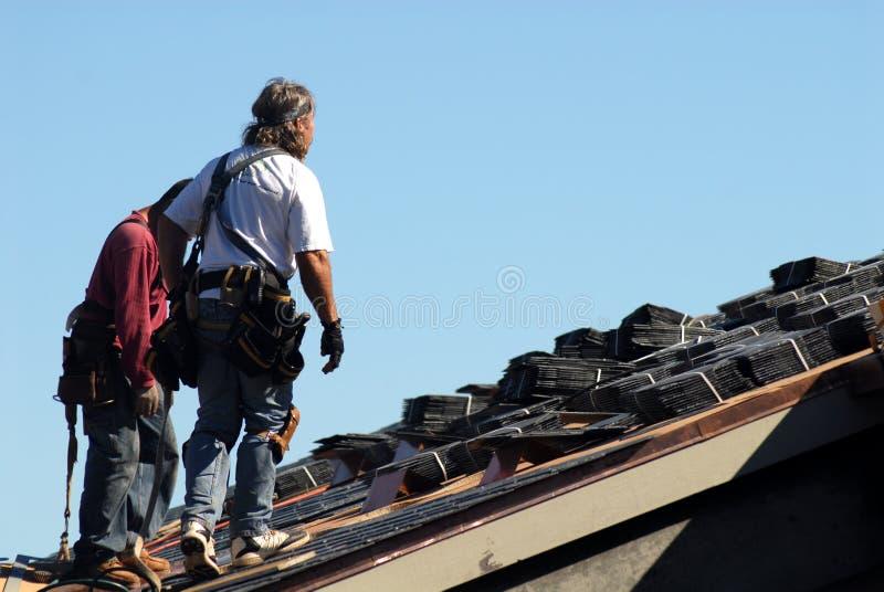Twee werklieden die op dak van de bouw lopen royalty-vrije stock foto
