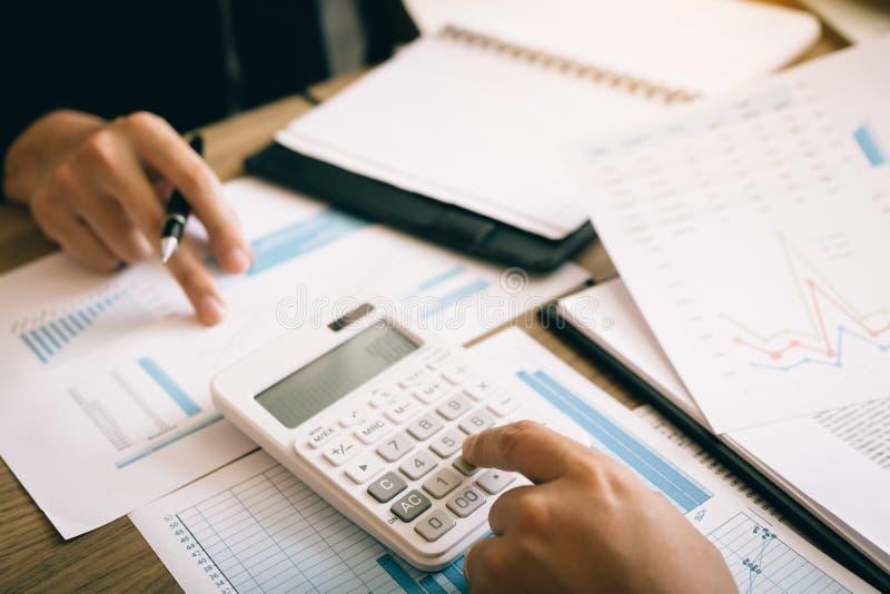 Twee werknemers berekenen over de winst van het bedrijf na het aftrekken van uitgaven stock afbeeldingen