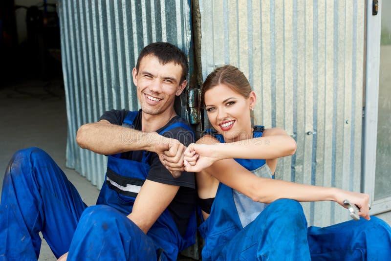 Twee werktuigkundigen zijn gelukkig na het werk en ontspannen dichtbij de autodienst stock foto's