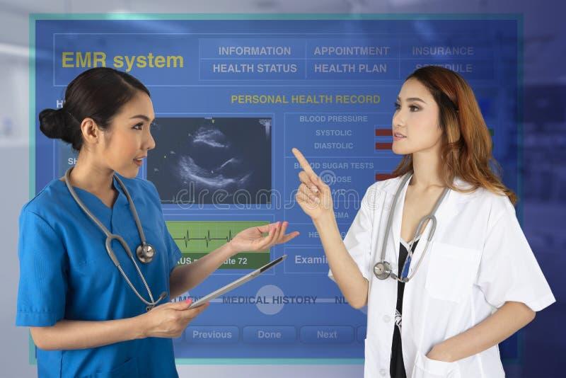 Twee wijfjes de arts bespreekt hun werk met elektronische medisch aangaande stock foto