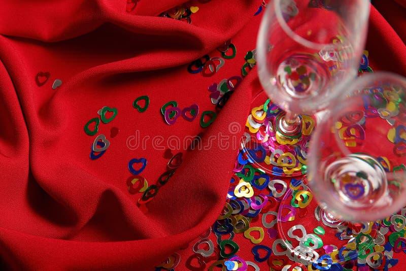 Twee wijnglazen met kleine gekleurde harten op een rode gordijnstof stock afbeelding