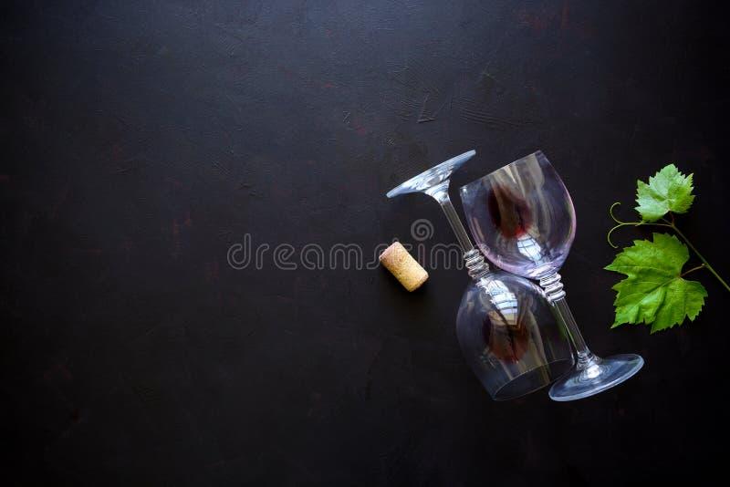 Twee wijnglazen met rode wijn, cork en druif verlaat het liggen op donkere houten achtergrond royalty-vrije stock fotografie