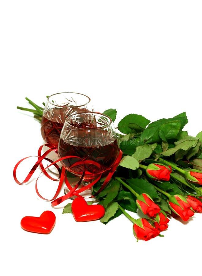 Twee wijnglazen met wijn, harten en een boeket o royalty-vrije stock afbeeldingen
