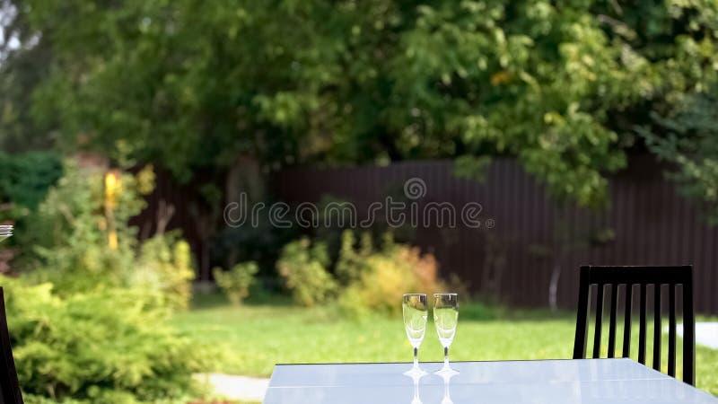 Twee wijnglazen op lijst in tuin, voorbereidingen voor openluchtdiner thuis stock foto