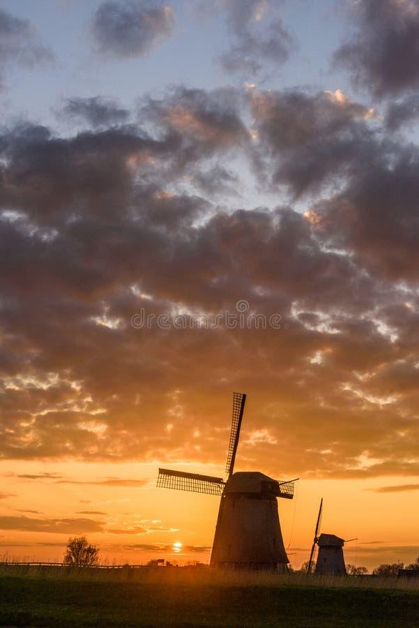 Twee Windmolens met de zon die in Nederland plaatsen stock fotografie
