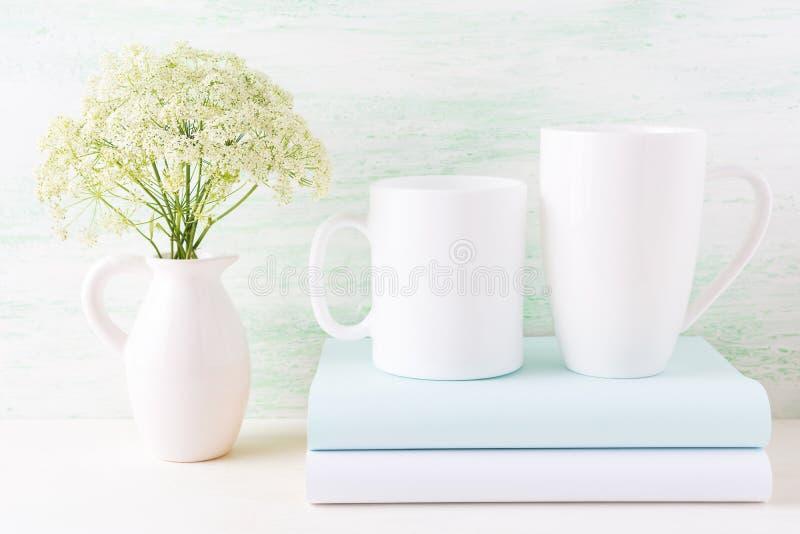 Twee wit mokkenmodel met boeken en witte bloemen in waterkruik royalty-vrije stock foto