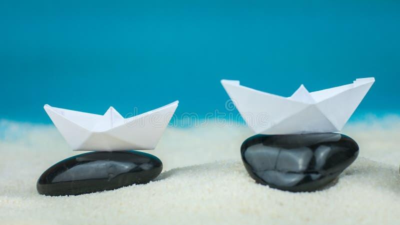 Twee Witboekboten Evenwichtig op Zwarte Stenen die op Zand leggen stock afbeeldingen