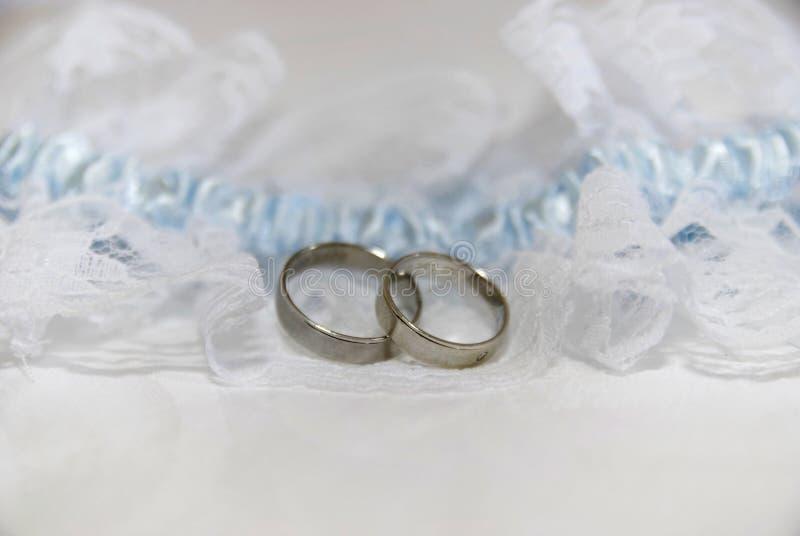 Twee witgoudtrouwringen op wit kantstootkussen en blauwe kouseband royalty-vrije stock afbeeldingen