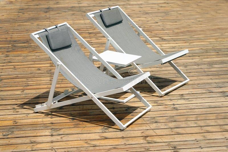 Twee witte de zomerstoelen op een houten vloer stock afbeelding