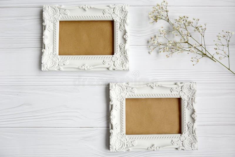 Twee witte gepatterde frames zwaaien omhoog op een lichte houten achtergrond stock fotografie