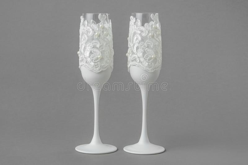 Twee witte glazen van de huwelijkswijn die met kant en parels worden verfraaid stock foto's
