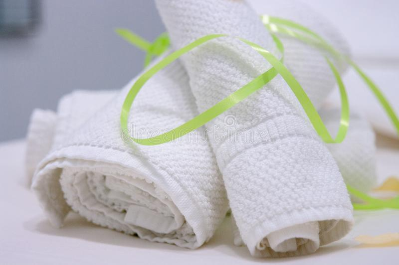 Twee witte handdoeken rolden en maakten met groene band op massagelijst vast stock fotografie