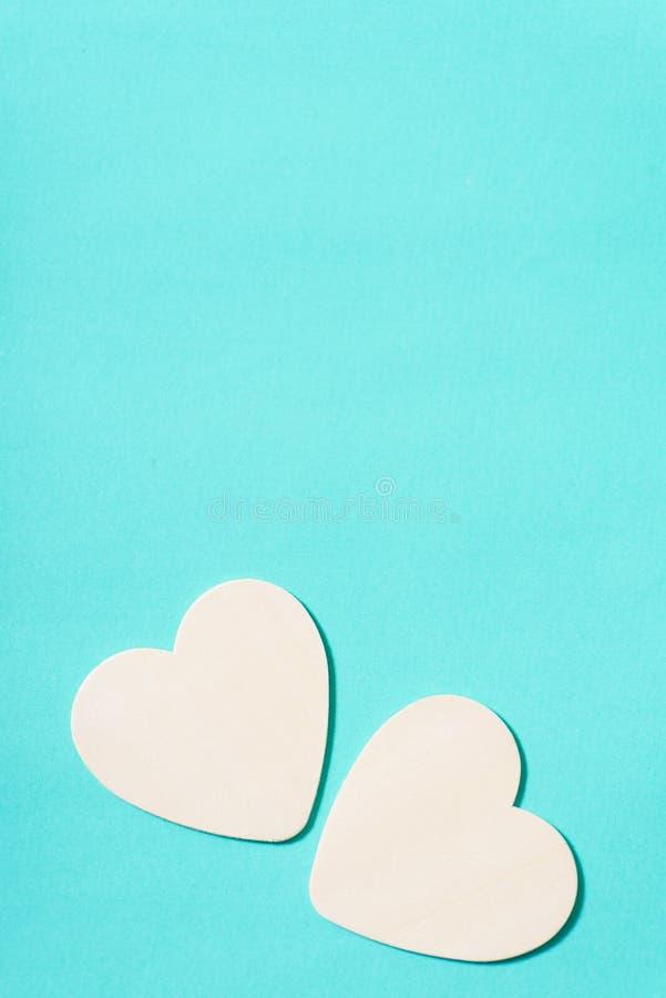 Twee witte harten op groene pastelkleurachtergrond stock fotografie