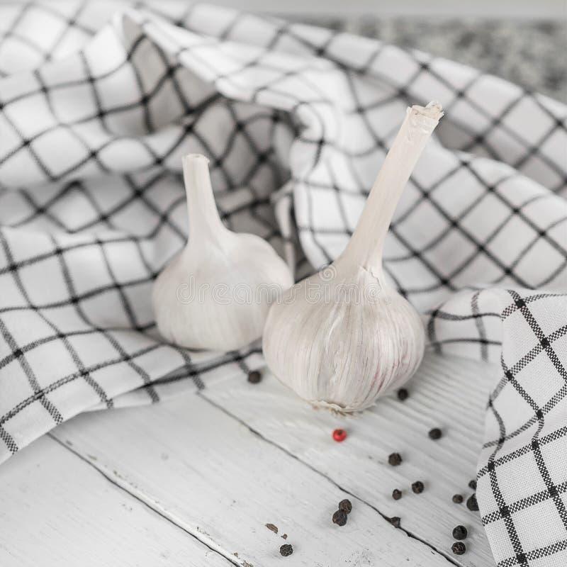 Twee witte hoofden van knoflook liggen op een houten witte achtergrond Nabijgelegen leugens een verspreide handdoek en peperbolle stock afbeelding