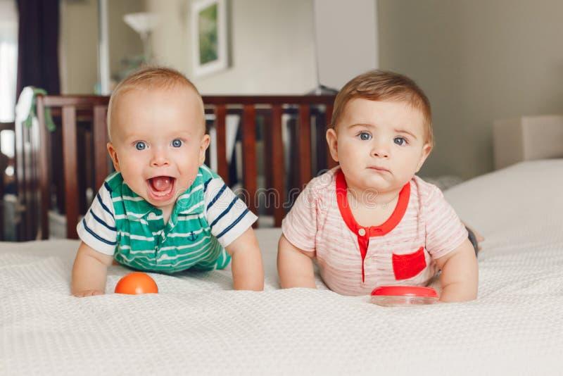 Twee witte Kaukasische leuke aanbiddelijke grappige babyjongens die samen op bed liggen die stuk speelgoed delen royalty-vrije stock foto's