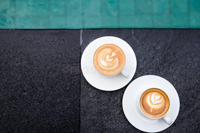 Twee witte koppen van smakelijke cappucino met kunst latte op de rand van zwembad stock foto