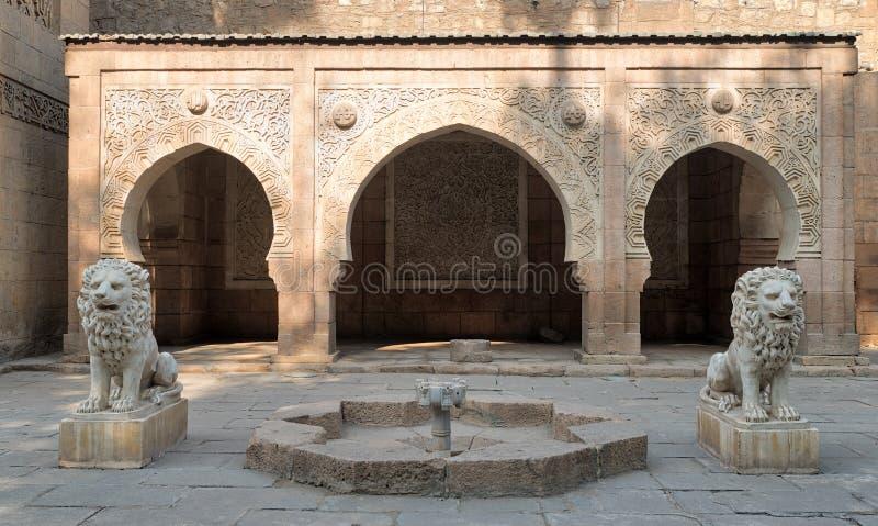 Twee witte marmeren leeuwenstandbeelden en decoratieve fontein stock foto's