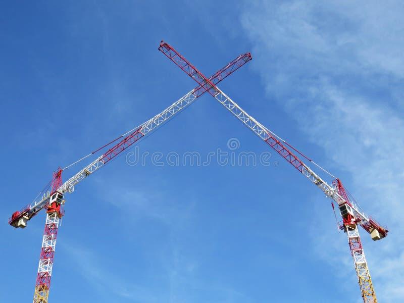 Twee Witte Rode Kranen die van de Bouwtoren hun Wapens op de Achtergrond van Blauwe Hemel met Witte Wolken kruisen royalty-vrije stock afbeeldingen