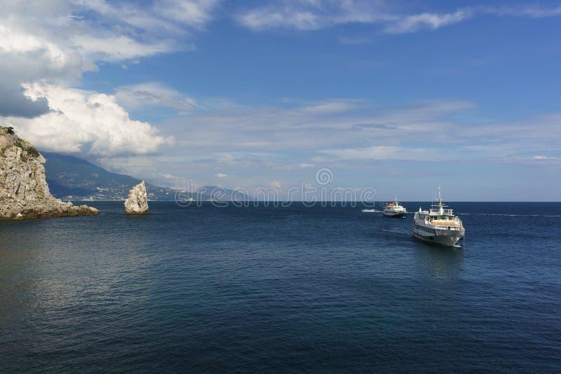 Twee witte schepen varen het kalme blauwe overzees op een Zonnige dag Kaap drempel-Burun en rotszeil in de toevlucht van de Zwart stock foto's