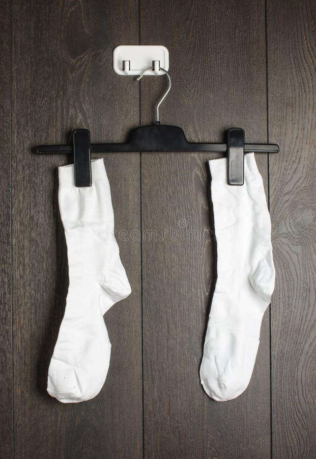 Twee witte sokken die op de muur worden gehangen stock foto