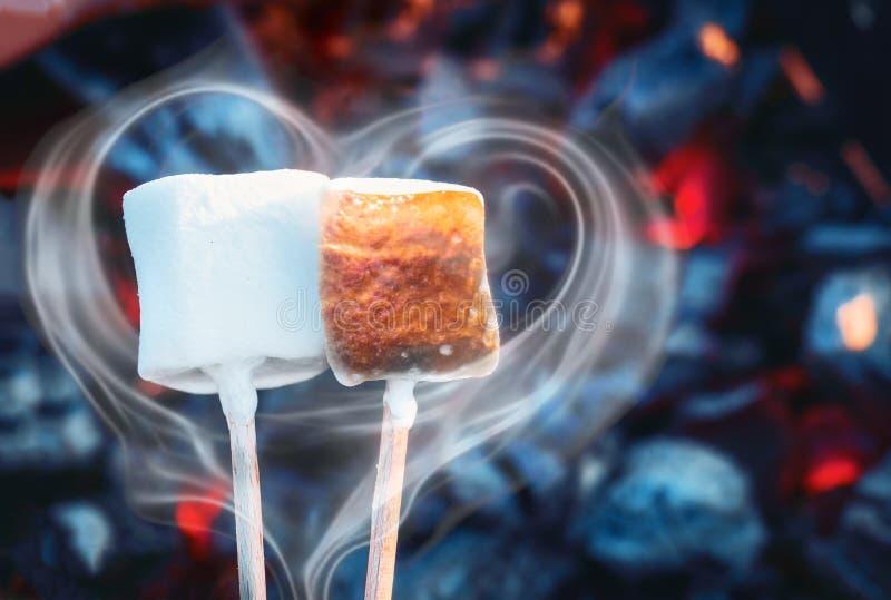 Twee witte zoete heemst die over brandvlammen roosteren Rook in vorm van hart Heemst op geroosterde vleespennen stock fotografie