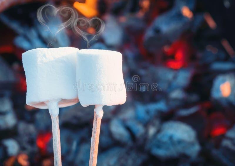 Twee witte zoete heemst die over brandvlammen roosteren Rook in vorm van harten Heemst op geroosterde vleespennen royalty-vrije stock foto's