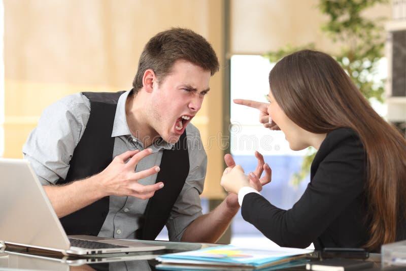 Twee woedend zakenlui die op kantoor debatteren stock afbeeldingen