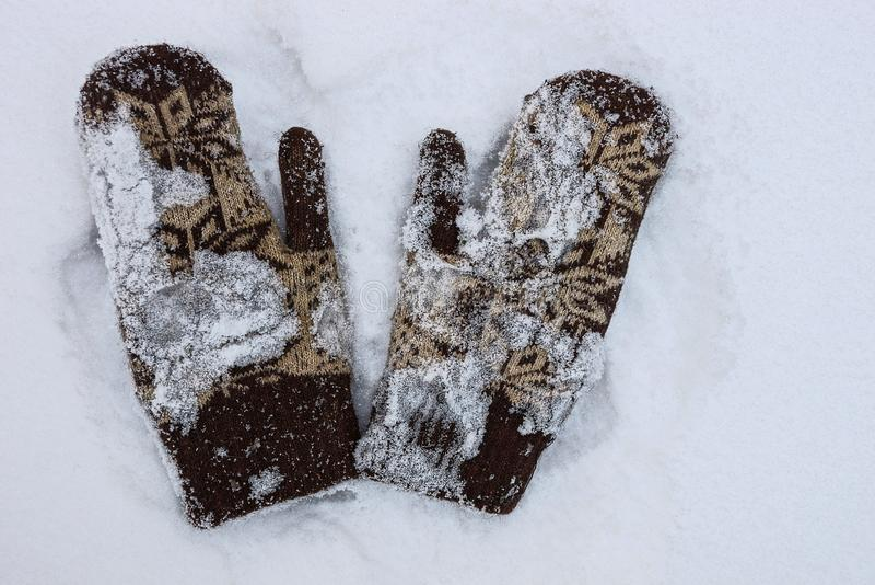 Twee wollen vuisthandschoenen op witte sneeuw en straat stock foto's