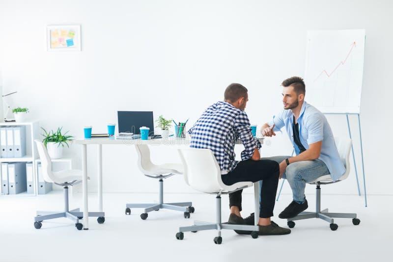 Twee zakenlieden die bedrijfsproject bespreken op vergadering stock foto
