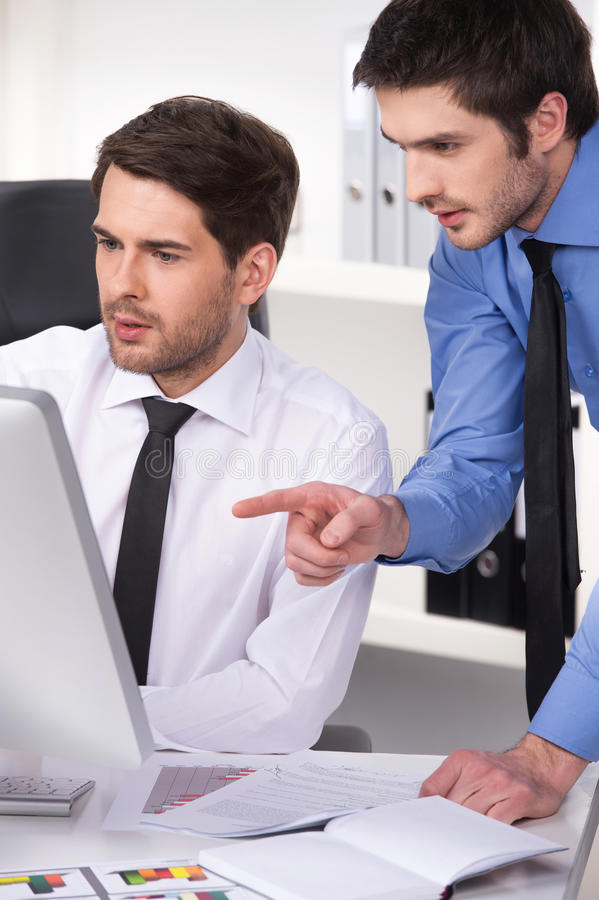 Twee zakenlieden die bespreking in bureau hebben stock foto