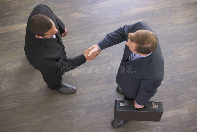 Twee zakenlieden die binnen handen schudden royalty-vrije stock afbeeldingen