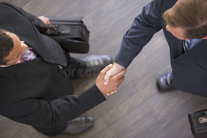 Twee zakenlieden die binnen handen schudden stock foto