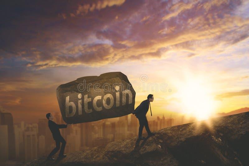 Twee zakenlieden die bitcoin woord op de klip dragen royalty-vrije stock fotografie