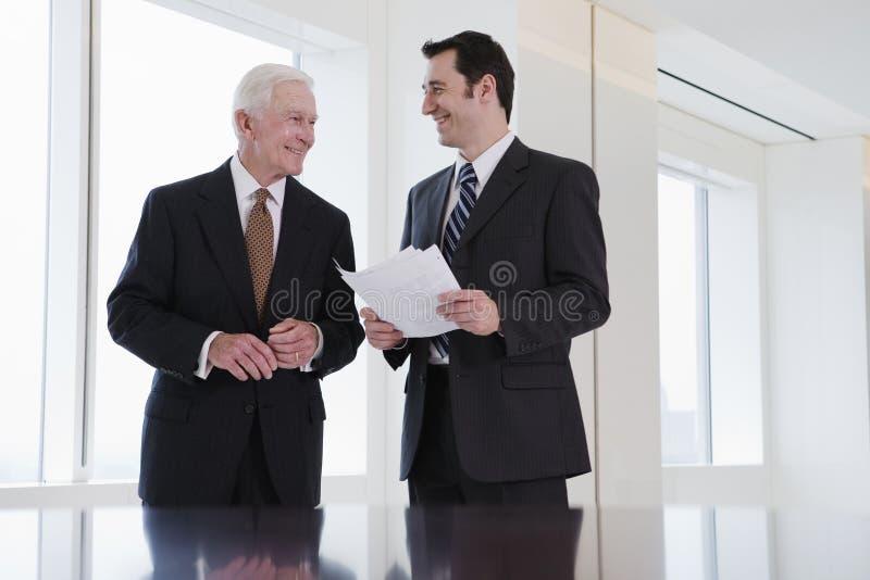 Twee zakenlieden die in een conferentieruimte spreken. stock foto's
