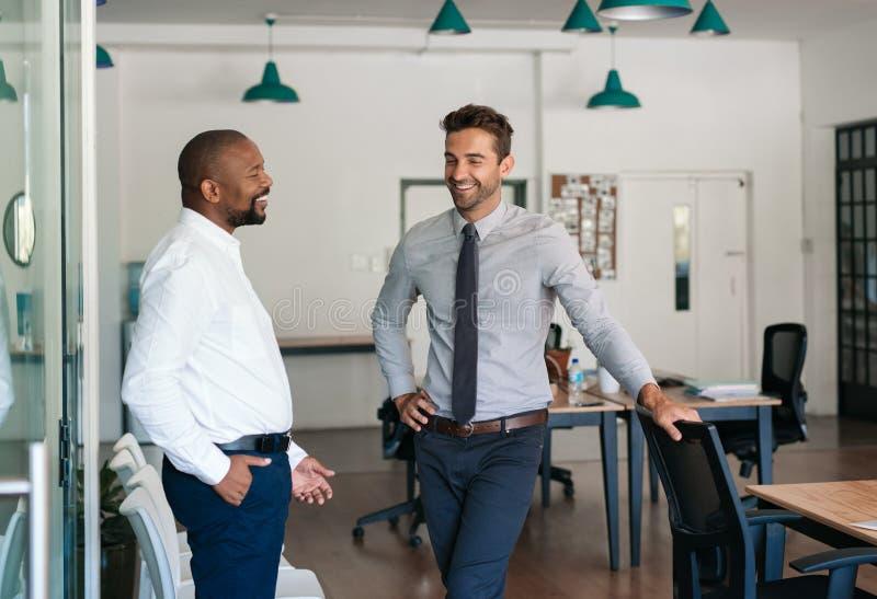 Twee zakenlieden die en samen in een bureau spreken lachen royalty-vrije stock foto's