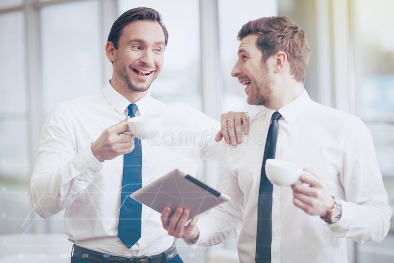 Twee zakenlieden die koffie in een bureau drinken stock foto's