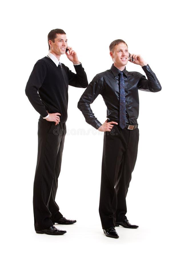 Twee zakenlieden die op de telefoon spreken royalty-vrije stock afbeeldingen