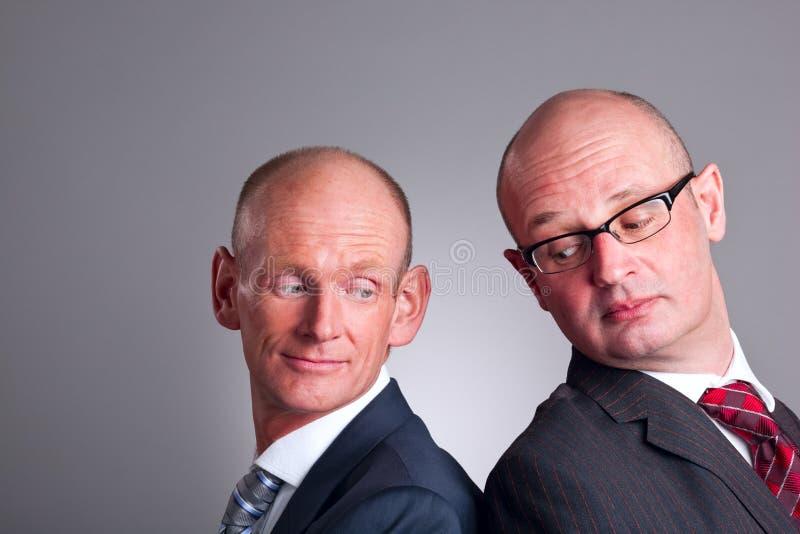 Twee zakenlieden die over schouder kijken stock foto