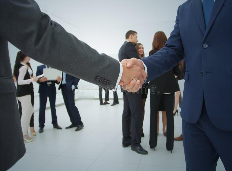 Twee zakenlieden die overeenkomst, hun collega's maken die zich dichtbij bevinden stock afbeelding