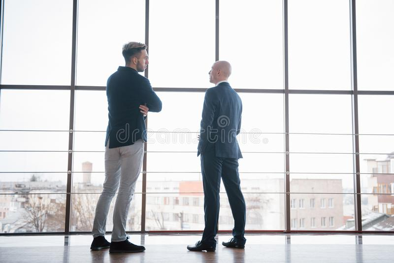 Twee zakenlieden diep in bespreking samen terwijl status in een bureaubestuurskamer met vensters die de stad overzien stock foto