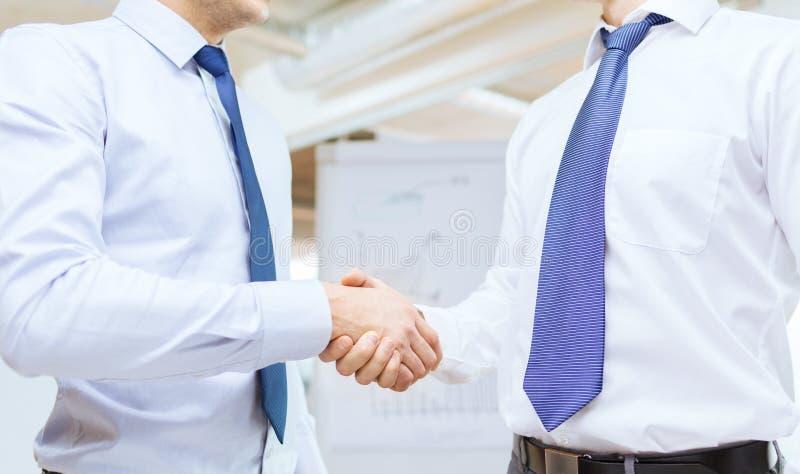 Twee zakenlieden het schudden dient bureau in stock afbeelding