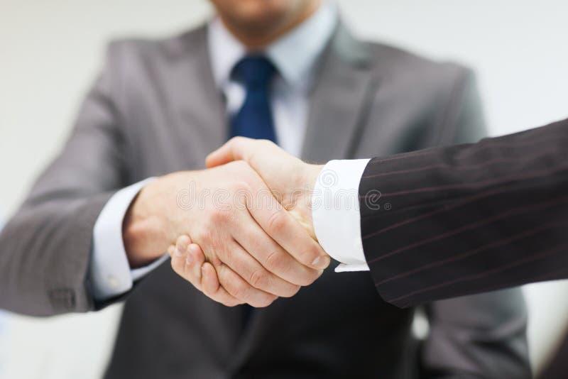 Twee zakenlieden het schudden dient bureau in royalty-vrije stock afbeelding
