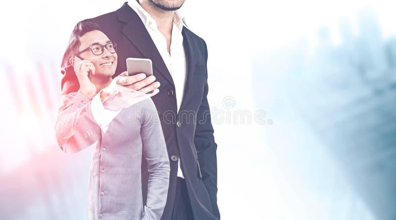 Twee zakenlieden met telefoons in vage stad stock foto's