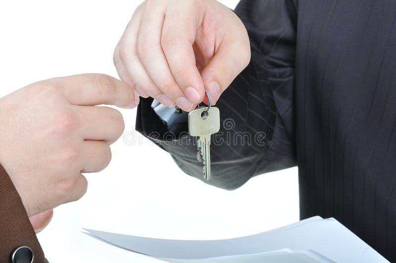 Twee zakenliedenhanden en de sleutel stock foto's
