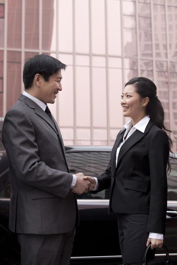 Twee zakenlui die handen in openlucht schudden stock foto
