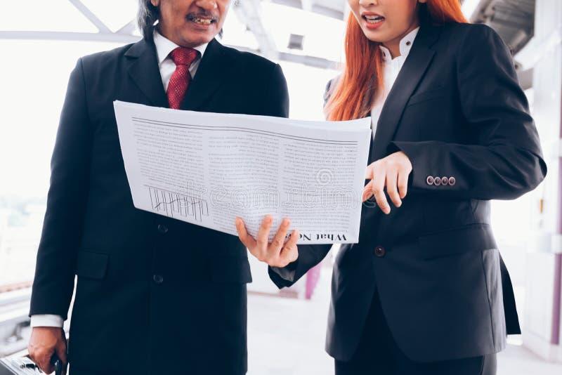 Twee zakenlui die op krant letten en over het breken spreken stock foto