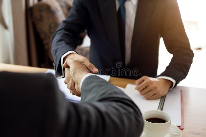 Twee zakenman het schudden dient bureau in stock foto's