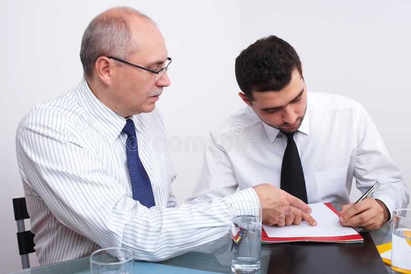 Twee zakenmanzitting bij lijst tijdens vergadering royalty-vrije stock afbeelding