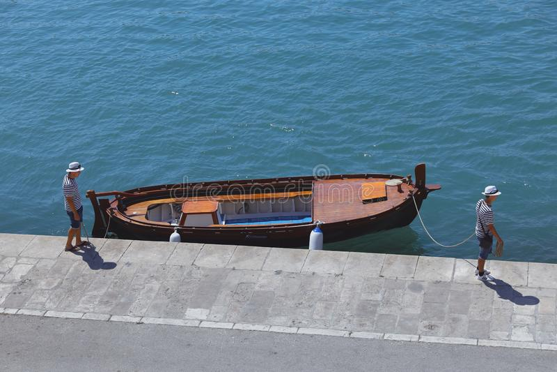Twee zeeliedenmensen en de boot bij de donkerblauwe werf in Spleet royalty-vrije stock foto's